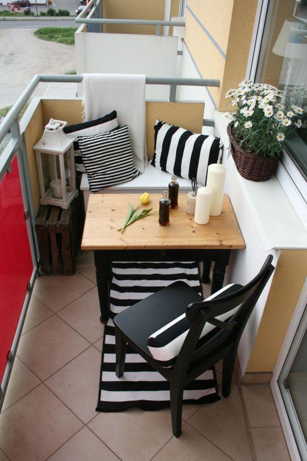 Aménagement balcon classique avec table en bois rectangulaire, banc blanc et chaise noire. Carrelage et tapis noir et blanc à rayures.