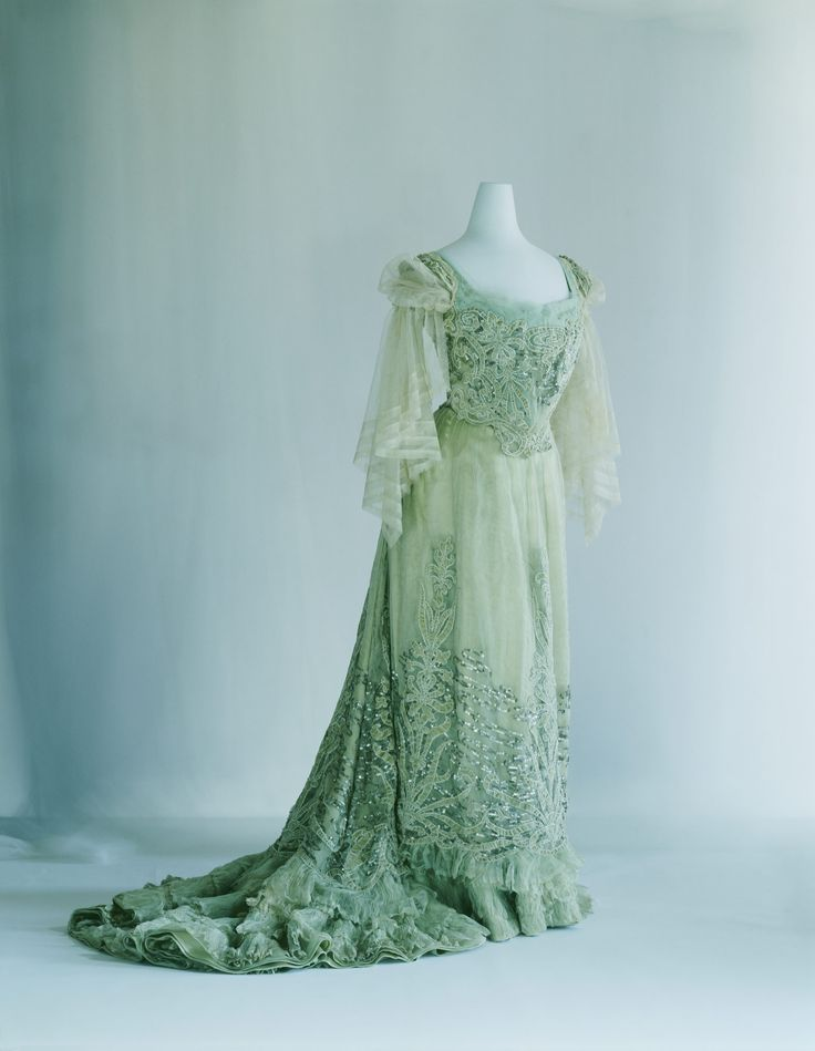 Evening Dress    c. 1900    Designer:       Jean-Philippe Worth  Brand:       Worth  Label:       C. Worth 50 939  Material:       Pale green silk chiffon and velvet; S-curve silhouette; appliqué of plant pattern; sequin and cord embroidery with water's-edge pattern.