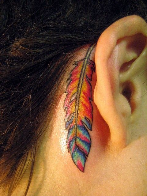 Colorful feather tattoo behind the ear. Its really pretty, and bright. Very