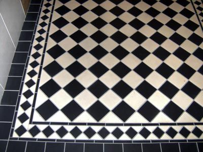 A simple and stylish black and white checkerboard pattern tiled hallway floor in Cork City.