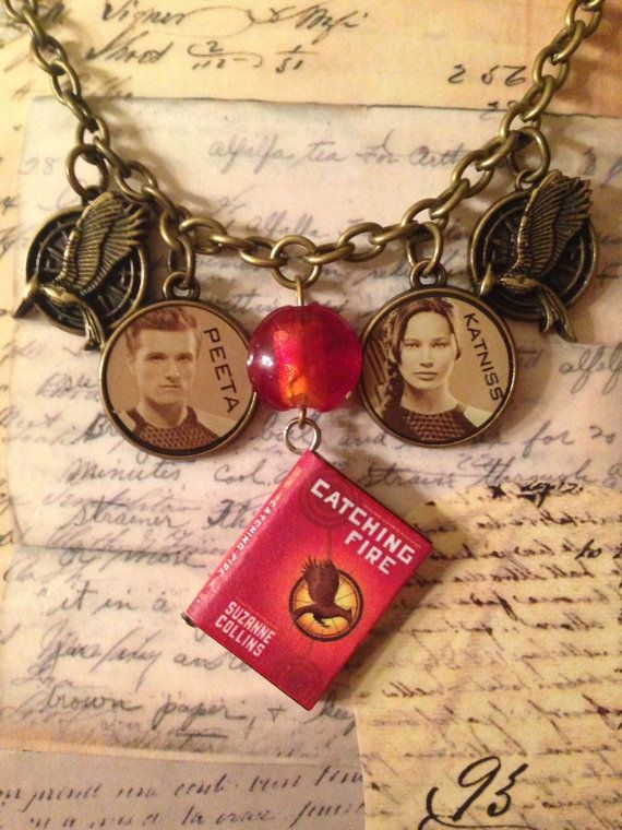 "Hunger Games Catching Fire Necklace on an 18"" brass chain.  It is part of the Charming Collection by LoveEuniceDesigns, $18.00"