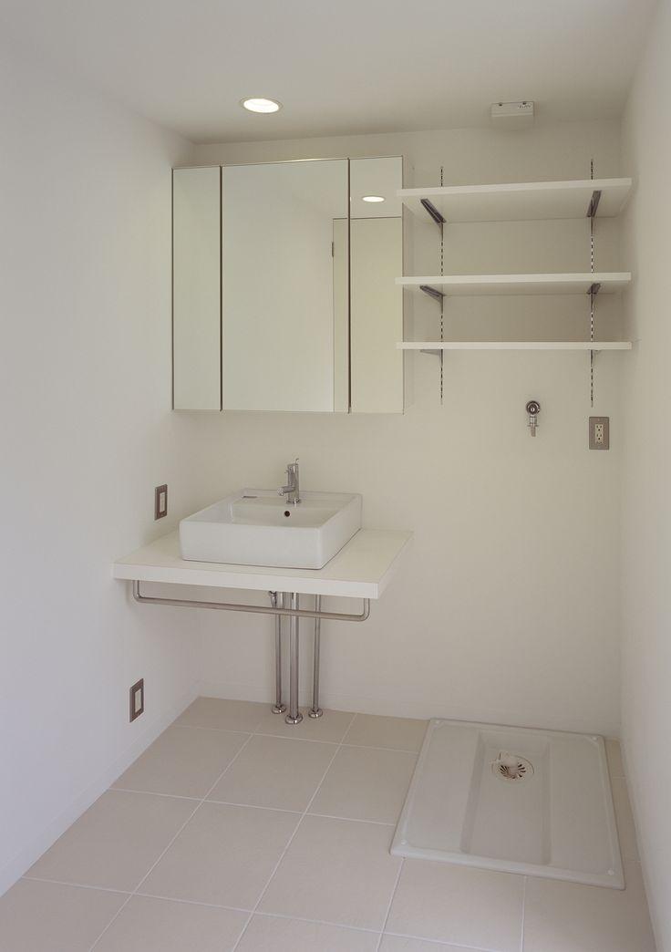バスルームと同じ白い床タイルを使用した、コンパクトにまとめた洗面所