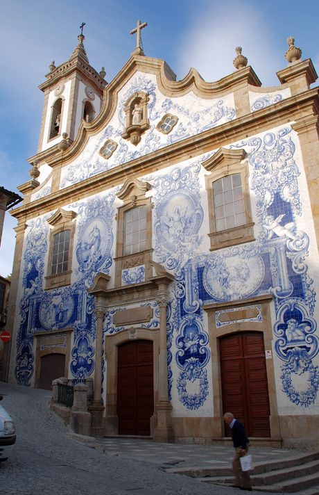 Façade of the Covilhã Church in Lisbon, Portugal ~ Photo: Anabela Maximiano ~ Ceramic tiles depicting various saints, (azulejos), adorn many Portugese walls & buildings. On hot days the sunlight bounces off the tiles, keeping the interiors cool. The art of decorative tiling was introduced in Portugal by the Moors over 5 centuries ago / Enter Portugal