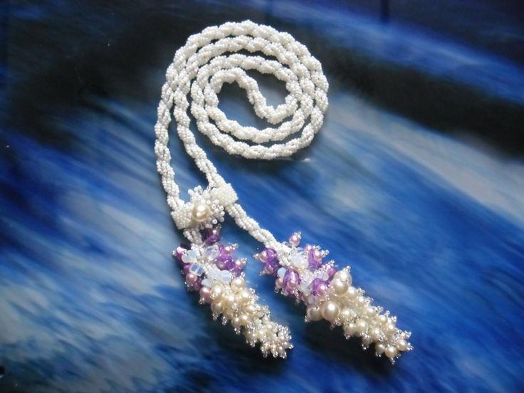 Nebeské snění. Spirálový náhrdelník je ušitý z rokailu v různých odstínech bílé barvy,obě šňůry jsou spojeny peyote stehem s všitou bílou perličkou, na každém konci šňůry jsou střapce pošité bílými a růžovými perličkami v různých velikostech dále jsou tam všité zlomky bílého polodrahokamu. Délka náhrdelníku je cca 100 cm. Cena 1200,- kč