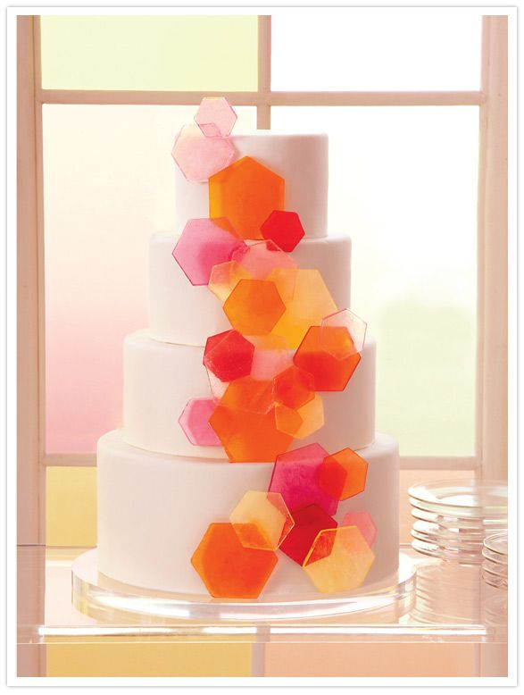 martha stewart weddings - gorgeous, unique cake. Geometric hexagons on white fondant covered rounds.  Pink, yellow, orange, red.  Love it!  #weddingcake #herecomesthebride