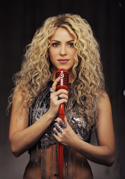 Target to offer deluxe edition of Shakira's upcoming album. Shakira holds a red microphone and wears a cropped top in the promotional image.