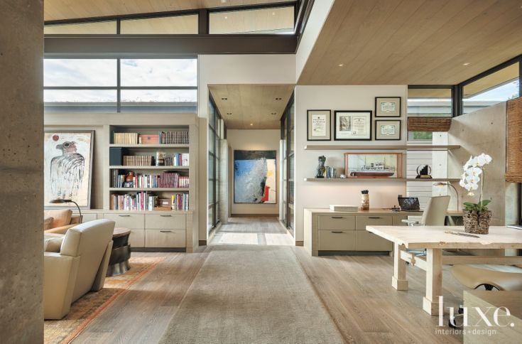 A library and office connect via a bridge to the master suite. Cabinetry features luggage-stitched leather with cerused white oak shelving. The eagle painting, by Jay Steensma, is from Shop Curator, and the William Ivey abstract at the end of the bridge is from Woodside/Braseth Gallery.