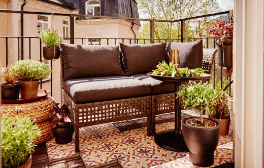 A balcony with outdoor seating filled with cushions and a lot of plant pots with green plants.