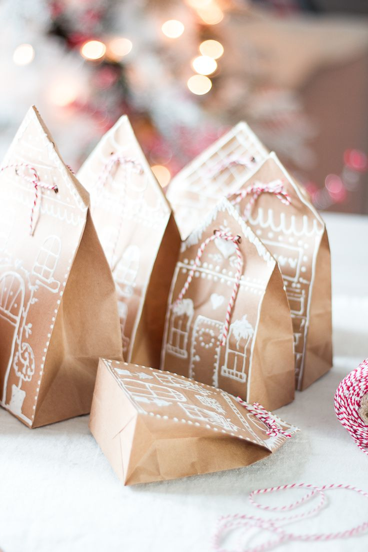 Gingerbread House gift bag idea l cute little gingerbread houses made of paper bags.  Using puffy paint, draw your desired design making it as simple or as complicated as you'd like. You can also have your kids draw on it with a white crayon or paint and decorate it with cute stickers.  Once dried, fold opening of bag to form a triangle, punch two holes and tie with ribbon or twine. (Martha Stewart copy cat)…
