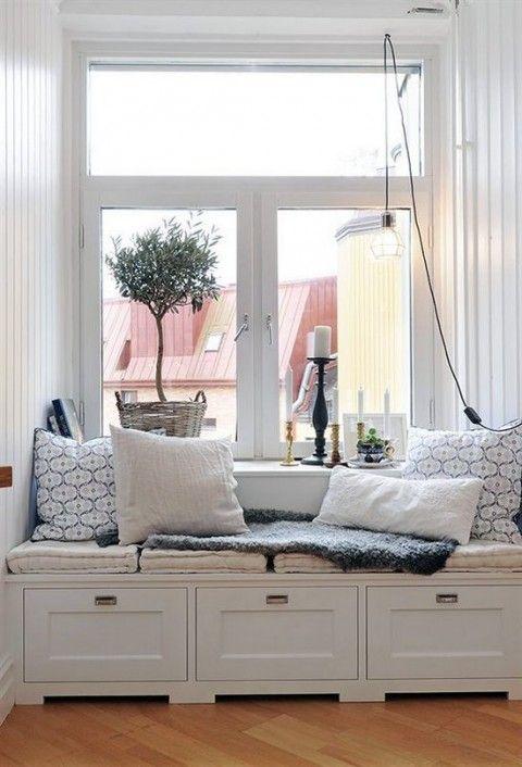 Je vensterbank kan ook een knusse zithoek worden. Kussens, kaarsen en een dekentje mogen niet ontbreken.