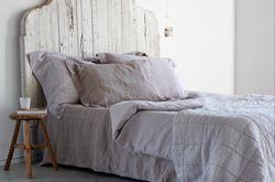 Rustiek bed met linnen beddengoed.