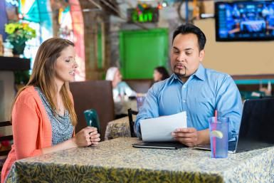 Restaurant manager reading resume and interviewing young woman for job - Steve Debenport / Getty Images