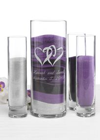"Show your love for each other by adding a sand blending ceremony to your wedding. It's a great alternative to lighting a unity candle and is perfect for outdoor or destination weddings. This romantic glass set includes: Three smaller cylinders for individual sand colors (bride, groom and minister, children or family)   Dimensions: 7 1/2"" tall X 1 3/4"" diameter. One large cylinder with linked hearts design. Dimensions: 9"" tall X 3"" diameter. Larger cylinder holds 3.5 lbs. of sand and…"