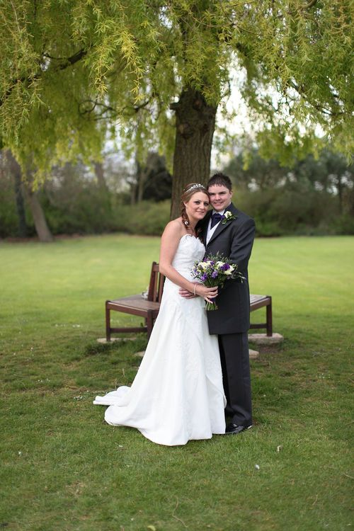 A bride and groom under a tree in the grounds of Bickley Manor, near Bromley