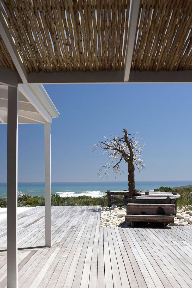 Wooden deck perfectly compliments this all-white beach cottage.