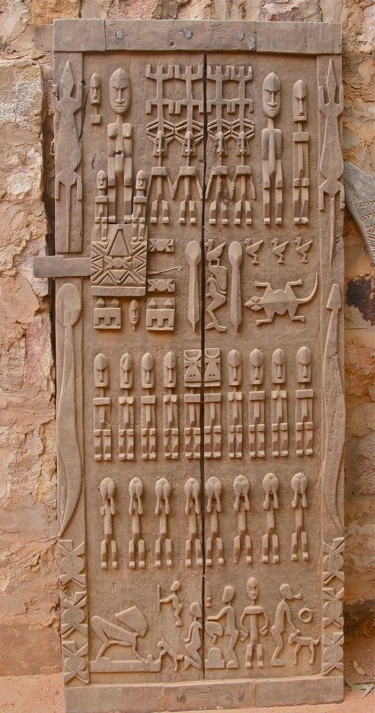 Dogon Door, Koundou Guina, Mali.  Since the Dogon language is oral, the Dogon often record their history in wood carvings, such as this door. This door deals with Dogon Cosmology and the Dogon migration that took place during the 12th to 15th centuries from ancestral lands to their current location on the Bandiagara Escarpment.  | © **El-Len** on flickr
