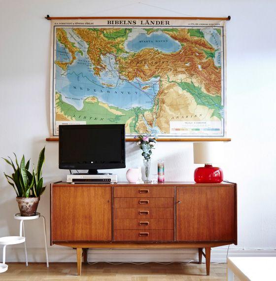 Antiikkinen kartta seinällä. Kartan alla vanha senkki, 60-luvun valaisin ja vieressä IKEA PS -kukkajalka.
