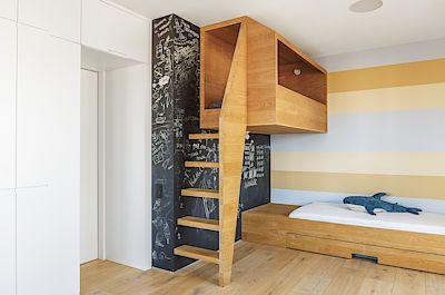 V pokoji chlapců umístili architekti jendu z postelí do dřevěného boxu zavěšeného do výšky na zdi.