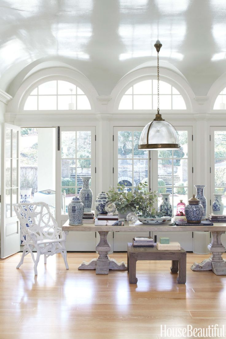 "In the living room of an Atlanta house by designer Beth Webb, an elm plank table from Clubcu, which often doubles as a dining table, dramatically displays a collection of Chinese porcelains. ""The pieces don't have to match, but they do have to play together well,"" Webb says."
