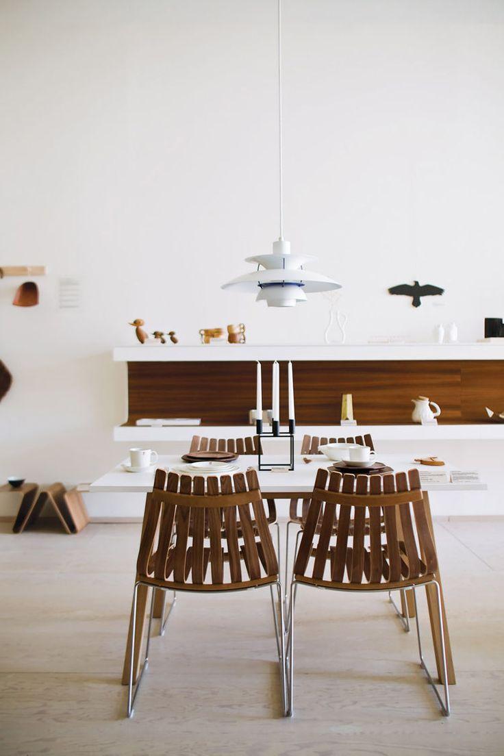 A white Louis Poulsen PH5 Pendant Light completes a refined Scandinavian dining room arrangement.