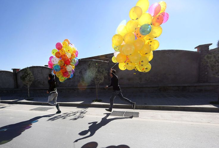 #Afghan boys run with a bunched of #coloredballoons that they hope to sell on the streets of #Kabul, #Afghanistan.