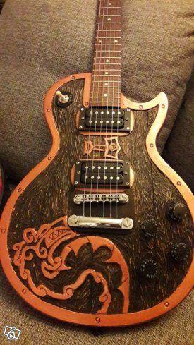 Här är en chans att äga en helt unik gitarr.  Grunden är en Koreansk Epiphone. Detta i sig är ingen unikt. Det som gör denna unik är det handkarvade träjobb som är gjort i gitarrkroppen (av mig), med ett motiv med nordiska klanger, tänk sköld. Annars...
