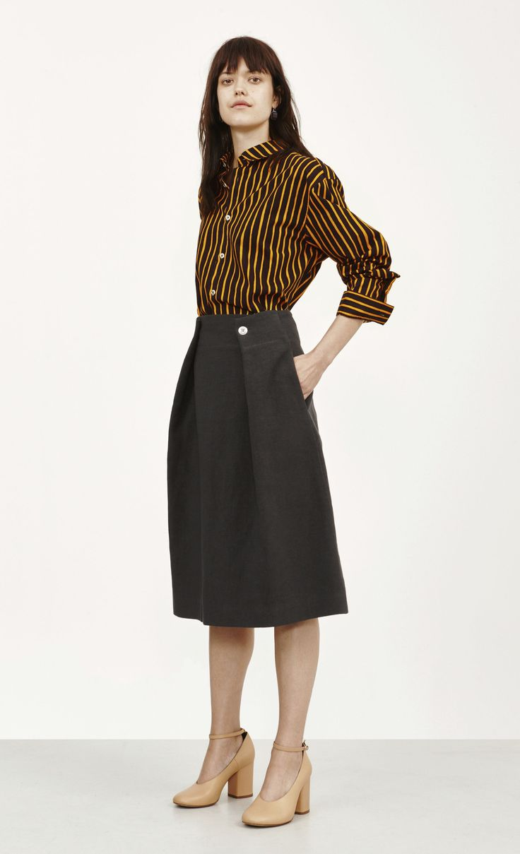 A flared, below-knee black skirt made of a woven viscose-cotton blend. The two front waistline pleats are secured with metal buttons. It has a back zip closure and side slit pockets.