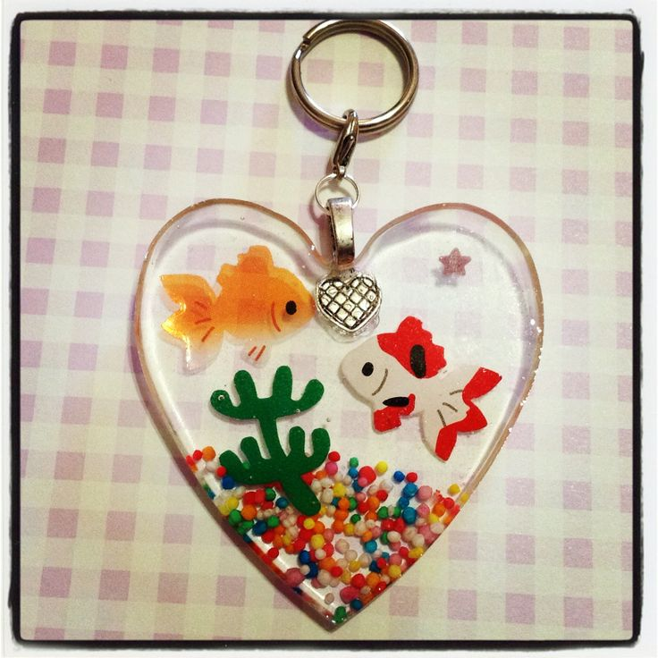 A gold and a white, red and black koi in a heart shaped 'aquarium'. The keychain can be used to hang all your keys from!     Colourful candy sprinkles used as the 'gravel' in the aquarium is also embedded in the resin, and this keychain is approx. 5.8cm wide and 6.5cm in length, and 0.5cm thick.  ...