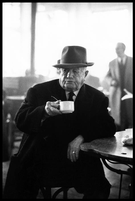 Elliott Erwitt GREECE. Kalamata. 1966. I liked this photo as the man is the main focus but there are people out of focus in the background, the man isn't looking directly at the camera so it doesn't look like it's faked. as the man's wearing a suit with a white shirt underneath, when put in black and white it has a somewhat dark look about it when compared to the white cup.