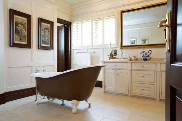 Antique bath, custom hand-painted cabinetry and panelling details create the ultimate in bathroom luxury