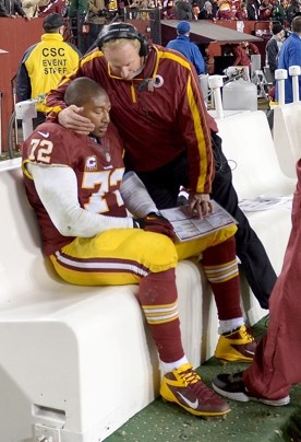 Redskins defensive coordinator Jim Haslett and defensive end Stephen Bowen (72) look over some charts