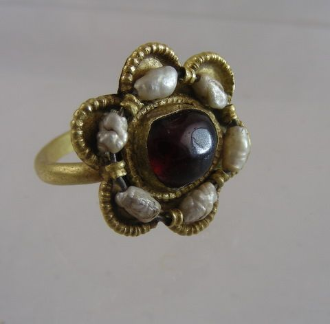 A remarkably rare late eleventh century, Ottonian gold ring with pearls, and a cabochon garnet.