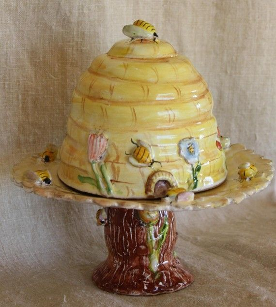 Vintage cake stand and topper in the form of a bee hive.