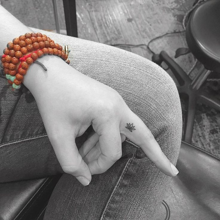 Tatuaje de una pequeña flor de loto minimalista situado en el dedo medio izquierdo. Artista tatuador: Jon Boy · Jonathan Valena