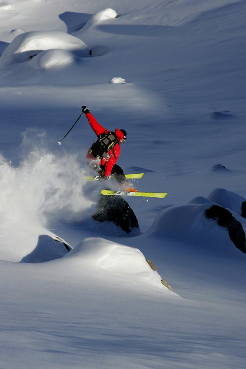 Skier jumping off a rock, Serre Chevalier ski resort, France.