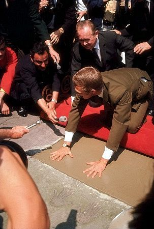 Steve McQueen getting footprints/handprints at Mann Chinese Theater with wife Neile-IMDb