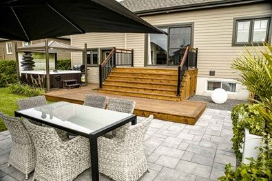 Galerie et patio de cèdre rouge qui rejoint la terrasse de dalles de béton. #patio #bois #permacon #terrasse #spa #paysagiste #aménagement #paysager #brissonpaysagiste