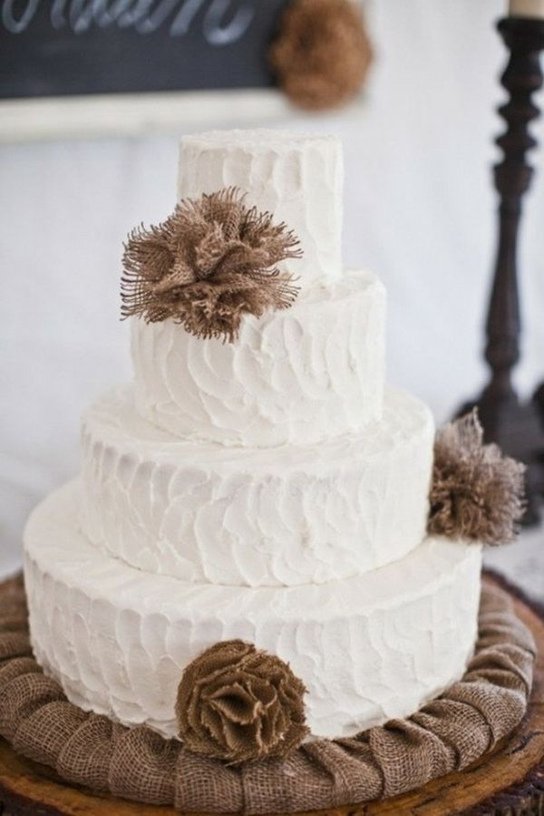 four-tiered white wedding cake decorated with burlap flowers