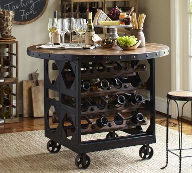 """Capturing the industrial warmth and character of vintage wine carts found throughout Northern California's Wine Country, our Trieste Wine Cellar Table makes a raw yet refined statement. Crafted from a mix of hardwood and steel, its substantial base artfully showcases a collection of wine. 48"""" diameter, 37"""" high  Stores 32 standard-sized wine bottles.  Internet Only."""