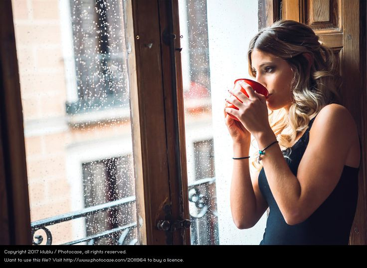 Attractive female drinking and looking at rain, thoughtful, hygge