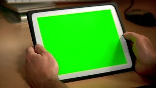 Stock Footage|A man uses his tablet PC at his desk.  Chroma key screen for placement of your own content. |Download using the VidLib app. 50.000 Royalty Free Clips