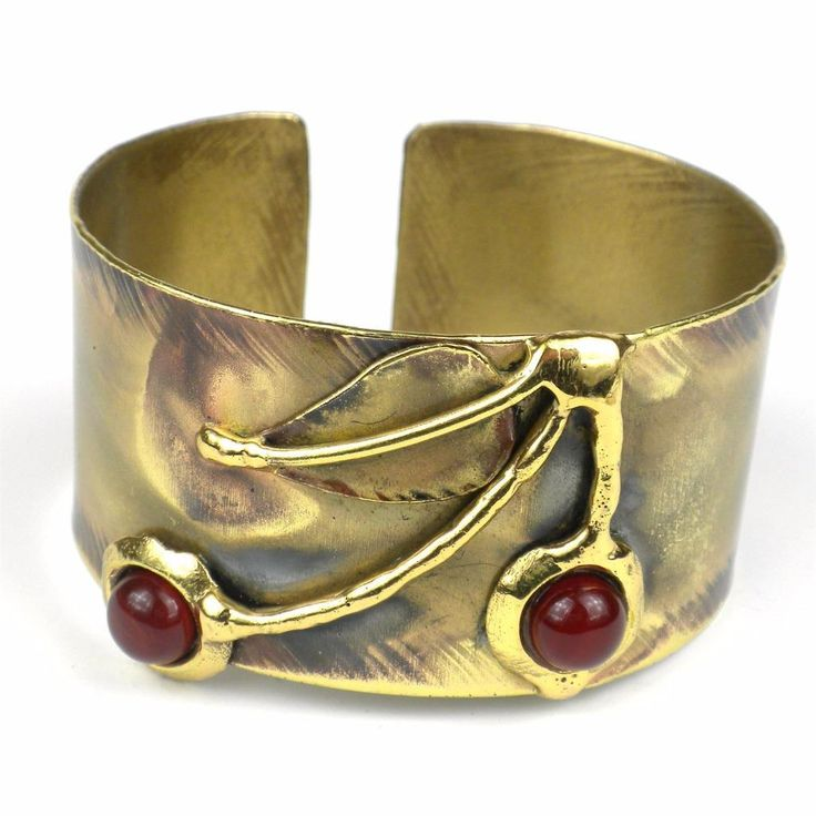 Handcrafted by South African artisans, this brass cuff features a cherry design of carnelian stones in stems of brilliant brass. The coloration on this 1.25-inch wide bracelet is achieved by applying extreme heat rather than paints or dyes.