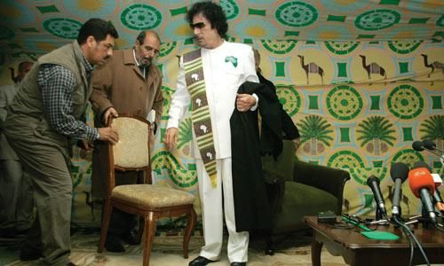 Libyan leader Muammar Gaddafi (right) takes a seat before a news conference in a tent in Kiev, Ukriane, yesterday. Col Gaddafi, who was born into a family of Bedouin herdsmen, in keeping with his tradition on foreign visits, pitched a tent in Kiev for his visit.