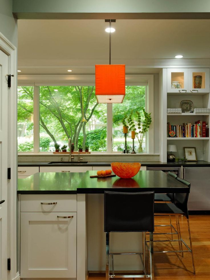 Vibrant orange accents stand out in this contemporary eat-in kitchen. The island with black quartz countertops and a beautiful outdoor view provides extra seating to make entertaining easy and stylish. A limestone backsplash runs behind the sink while a built-in bookcase and set of display cabinets help keep things tidy.