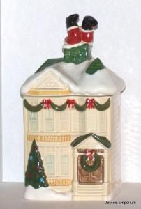 """While on his deliveries Christmas Eve Santa got stuck trying to sneak down the chimney of this Victorian home and now he is in a pickle. Take off the top and get a view of this little elf trying to figure out just how he's going to ever get loose.  This cute cookie jar measures 14"""" high x 6"""" deep x 6"""" wide.  It is stamped on the bottom HOMCO 1990"""