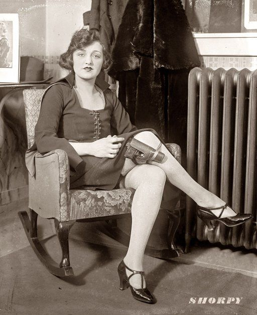 Safety first is the motto of Miss Mary Jayne of Keiths circuit. Mary Jayne, seated in rocking chair with pistol strapped to her knee, claiming exemption from concealed weapon regulation by saying her thirty-two isnt a concealed weapon in these days of knee-length skirts. National Photo Company Collection, February 14, 1922.