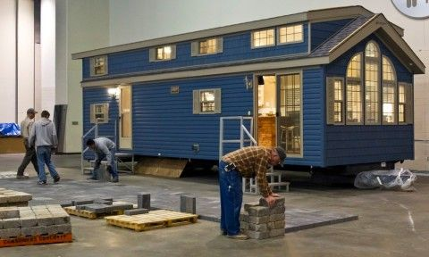 "The 400-square-foot ""park model"" has room to sleep eight, a full kitchen with an island, an 11-foot ceiling, a full bath with shower and landscaping to hide the wheels on which it rode into DeVos Place convention center."