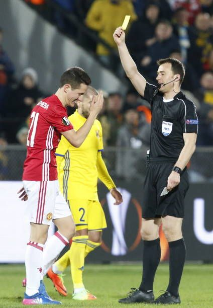 Referee Felix Zwayer shows a yellow card to FC Manchester United's Ander Herrera in Leg 1 of their 201617 UEFA Europa League Round of 16 football...