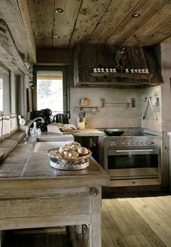 Cocina muy rústica con uso de la madera para suelo, techo y muebles. Incluso han forrado de madera la campana. #cocinas #rusticas #madera
