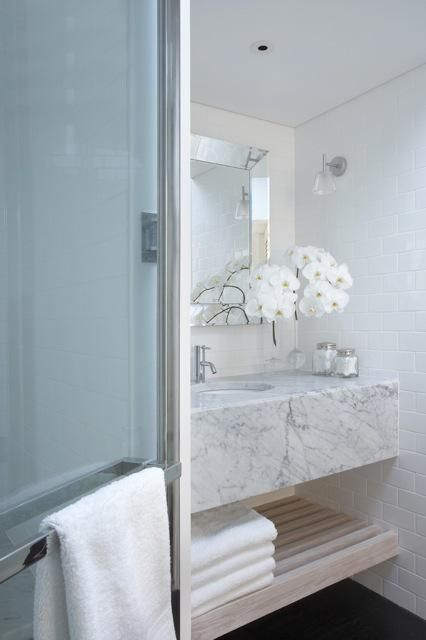 Stunning bathroom design features polished chrome glass shower enclosure next to floating marble vanity with shelf. Marble floating vanity with beveled mirror and subway tiled backsplash.